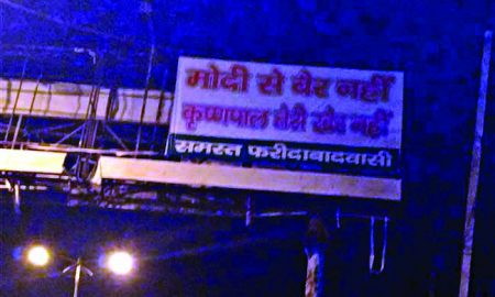 Political parapet mounted with slogan written on hoardings in Faridabad